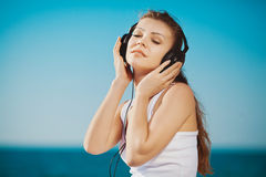 Portrait of beautiful woman sitting on the beach near the sea in headphones listening to music Royalty Free Stock Photography