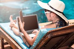 Portrait Beautiful Woman Sitting in deck chair and using laptop. Computer near swimming pool in vacation time blue water Royalty Free Stock Photos