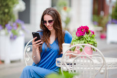 Portrait of beautiful woman sitting in outdoor cafe drinking coffee and using smartphone. Young girl looking instagram Royalty Free Stock Photography