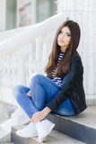 Portrait of a beautiful woman sitting on the steps. Beautiful young girl, Caucasian appearance, with dark, long, straight hair, brown eyes and beautiful dark Stock Images