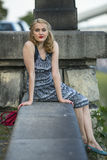 Portrait of beautiful  woman sitting on a stone embankment. Royalty Free Stock Images