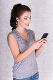 Portrait of beautiful woman with smart phone over white brick wa Royalty Free Stock Photography