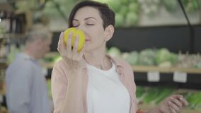 Portrait of beautiful woman smelling organic yellow bell pepper and smiling. Positive young Caucasian buyer choosing