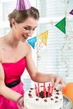 Portrait of a beautiful woman smiling while putting red candles on cake royalty free stock photo