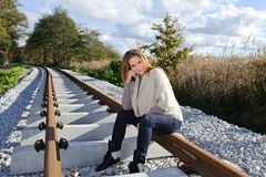 Portrait of beautiful woman smiling and sitting at railways. Beautiful time of a year, sunny day Royalty Free Stock Image