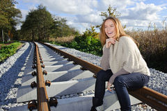 Portrait of beautiful woman smiling and sitting at railways Stock Image