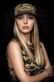 Portrait of beautiful woman soldiers in military attire on black background. Portrait of a beautiful blond woman soldiers in military attire on black background Royalty Free Stock Photo