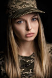 Portrait of beautiful woman soldiers in military attire on black background Stock Images