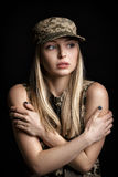 Portrait of beautiful woman soldiers in military attire on black background. cold and despair Stock Images