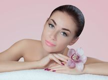 Portrait of a beautiful woman in a spa salon with an orchid in her hand. royalty free stock photography