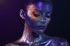 Portrait of beautiful woman with sparkles on her face. Girl with Art Make-Up in Color Light. Fashion Model with Colorful Makeup Royalty Free Stock Images
