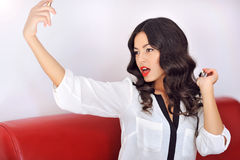 Portrait of a beautiful woman spraying perfume Royalty Free Stock Photography