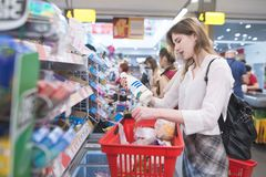 Portrait of a beautiful woman standing in line at the supermarket`s cashier and pulling out the red basket stock image