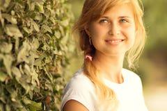 Portrait of a beautiful woman standing near a green bush Royalty Free Stock Image