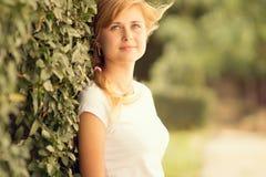 Portrait of a beautiful woman standing near a green bush Royalty Free Stock Photos