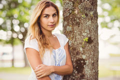 Portrait of beautiful woman standing by tree trunk Stock Image
