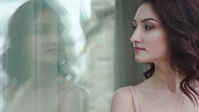 Portrait of beautiful woman stands on balcony and looks in glass door stock footage