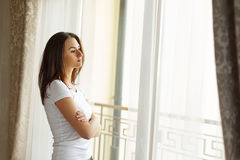 Portrait of a beautiful woman staying near the window and very seriously thinking about life. Stock Photo