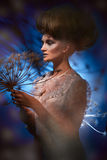 Portrait of a beautiful woman with stylish hairdo posing with big dandelion Royalty Free Stock Images