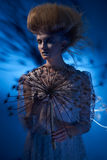 Portrait of a beautiful woman with stylish hairdo posing with big dandelion. On blue background Stock Photos