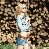 Portrait of a beautiful woman in sunglasses in denim shorts and. Jeans jacket on the sawmill. summer Stock Photos
