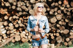 Portrait of a beautiful woman in sunglasses in denim shorts and. Jeans jacket on the sawmill. summer Stock Images