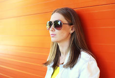 Portrait beautiful woman in sunglasses over orange background Stock Photography