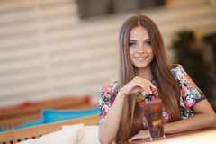 Portrait of a beautiful woman at a table in summer cafe Stock Photo