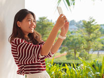 Portrait of beautiful woman take a photo, selfie by mobile phone Royalty Free Stock Images