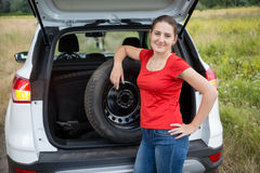 Portrait of beautiful woman taking out spare wheel to change on. Portrait of beautiful young woman taking out spare wheel to change on the broken car at field Royalty Free Stock Image