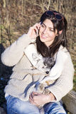 Portrait of beautiful  woman talking on the phone and hugging her dog Royalty Free Stock Photography