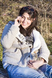 Portrait of beautiful  woman talking on the phone and hugging her dog Royalty Free Stock Images