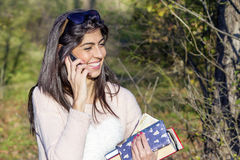 Portrait of a beautiful woman talking on the phone in the park Royalty Free Stock Photography