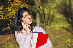Portrait of a beautiful woman talking on the phone in the park. Portrait of a beautiful woman walking in the autumn park ,talking on the phone royalty free stock photo