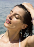 Portrait of a beautiful woman tanning her face at the beach Royalty Free Stock Image