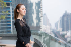 Portrait of beautiful woman on top of roof with building background Royalty Free Stock Images