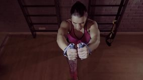 Portrait of beautiful woman training using pulley-weights. Portrait of beautiful woman training at the gym using pulley-weights. High-angle shot. Slow motion stock video