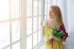 Portrait of beautiful woman with tulip bouquet and cup tea. Stock Photo
