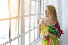 Portrait of beautiful woman with tulip bouquet and cup tea. sunlight. Stock Photos