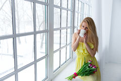 Portrait of beautiful woman with tulip bouquet and cup tea at the window. 8 march. copyspace. Stock Photos