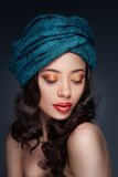 Portrait of a beautiful woman in turban. Portrait of a beautiful woman with arabian makeup in turban isolated on dark background Stock Photo