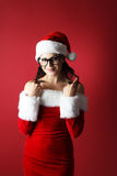 Portrait of a beautiful woman twisting her hair around her fingers wearing santa claus clothes Stock Photography