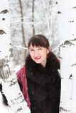 Portrait of a beautiful woman about two birches. Portrait of a beautiful woman in a winter forest near two birches Stock Photo