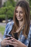 Portrait of a beautiful woman typing on the smart phone in a park Stock Photography