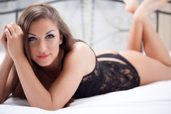 Portrait of beautiful woman in underwear lying on the bed Stock Image
