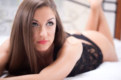 Portrait of beautiful woman in underwear lying on the bed Royalty Free Stock Photos