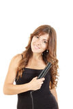 Portrait of beautiful woman using hair straightener stock images