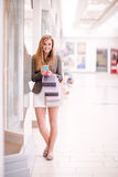 Portrait of beautiful woman using her phone while window shopping Stock Photography