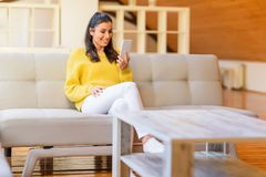 Portrait of a beautiful woman using her smartphone in the living. Room while relaxing on the sofa in a wooden attic loft.r Royalty Free Stock Photography