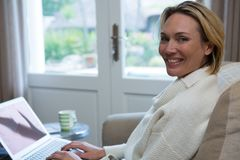 Beautiful woman using laptop on sofa royalty free stock photo